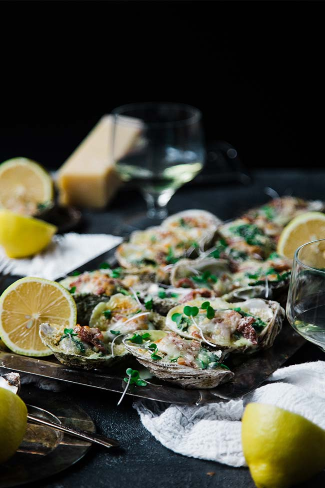 oysters rockefeller on the half shell served with cheese and lemons