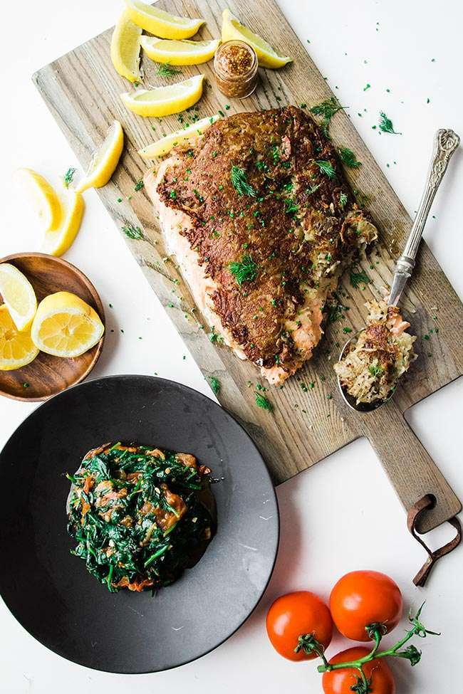 hash browns crusted salmon fillet with lemon slices and sautéed spinach