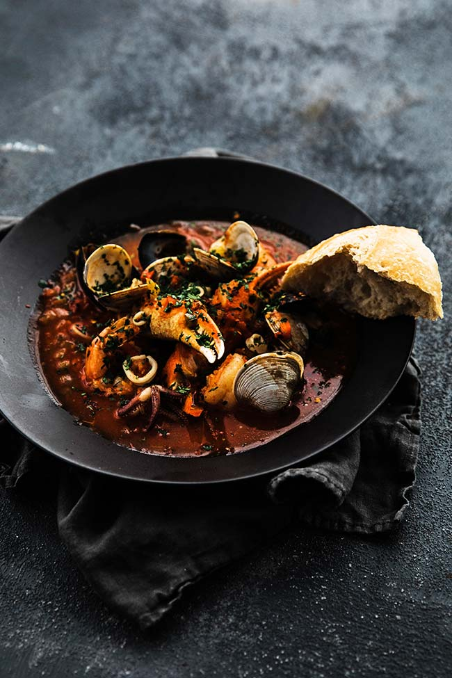 shellfish cooked in a tomato herb broth and served with bread