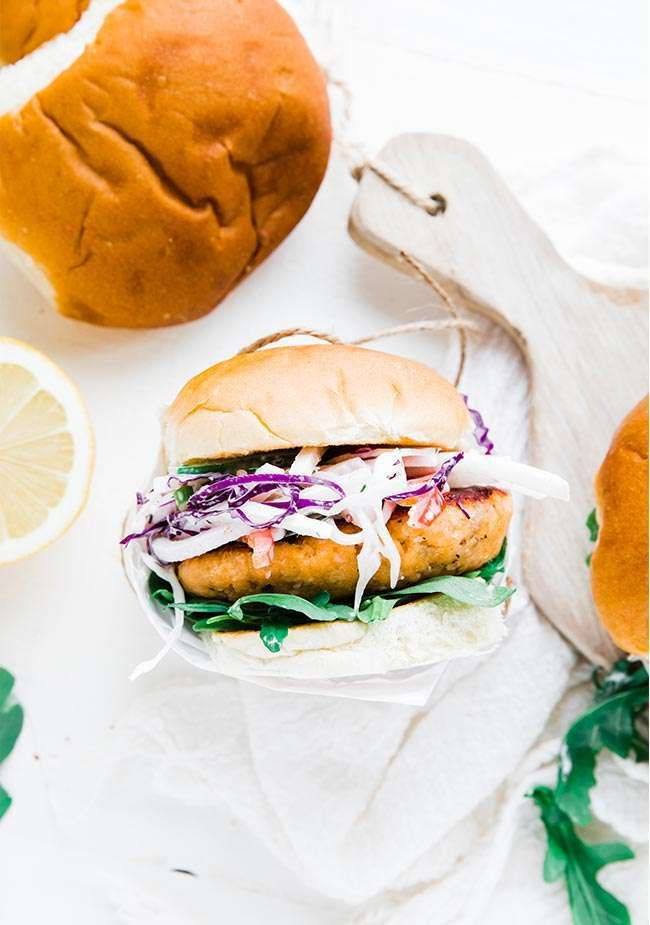 Salmon Patty Burger - this right here is so delicious. Learn how to make a super tasty homemade salmon pattie then serve it up with an even more amazing jicama coleslaw, arugula leaves all on a toasted bun. #salmon #salmonercipes #salmonpatties #salmoncakes #burger #burgerrecipes #grilledsalmon #seafood #seafoodrecipes #coleslaw #coleslawrecipe