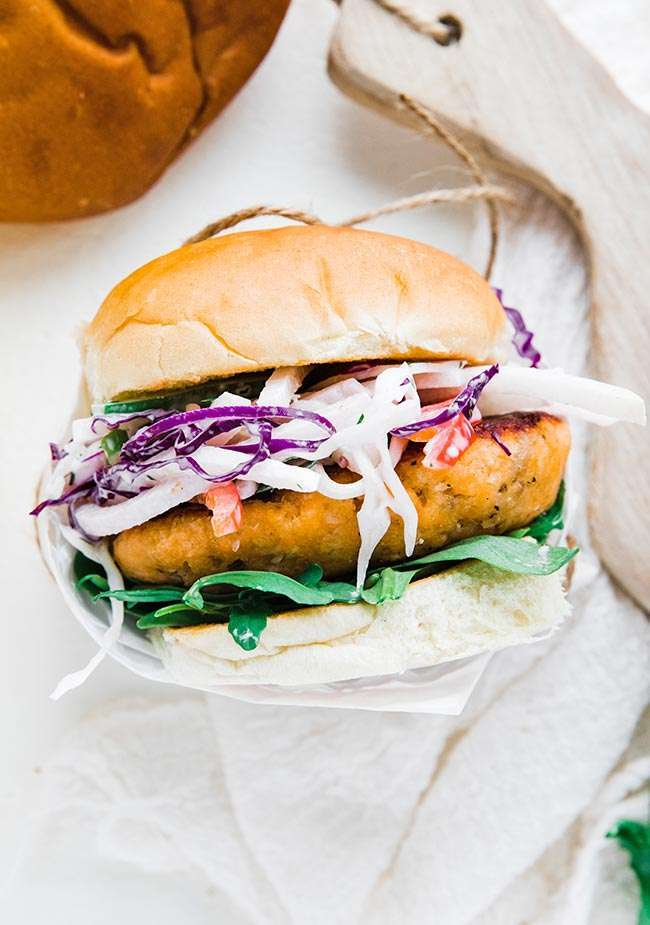 Salmon Burger with Jicama Coleslaw - this amazing grilled salmon burger is loaded up with a homemade salmon pattie that is grilled on the flat top and served with arugula and creamy jicama coleslaw on a toasted bun. #salmon #salmonercipes #salmonpatties #salmoncakes #burger #burgerrecipes #grilledsalmon #seafood #seafoodrecipes #coleslaw #coleslawrecipe