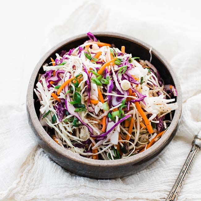 vinegar based coleslaw recipe in a bowl with apple cider vinegar