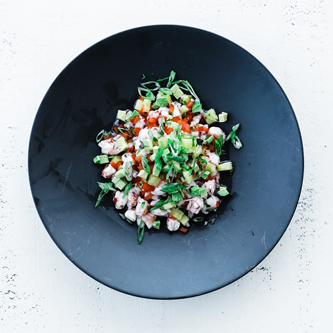 shrimp ceviche with vegetables and fruit in a plate