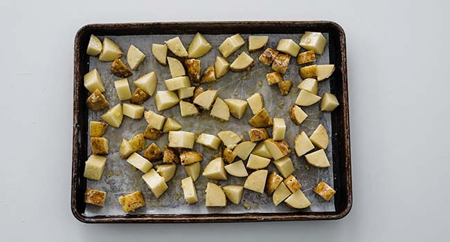cubed potatoes spread out on a sheet tray