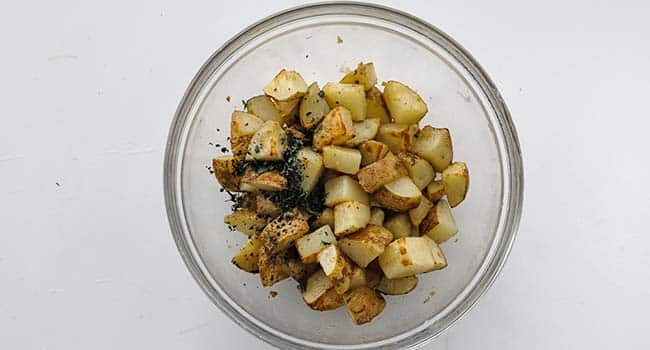 tossing potatoes in a bowl with fresh oregano