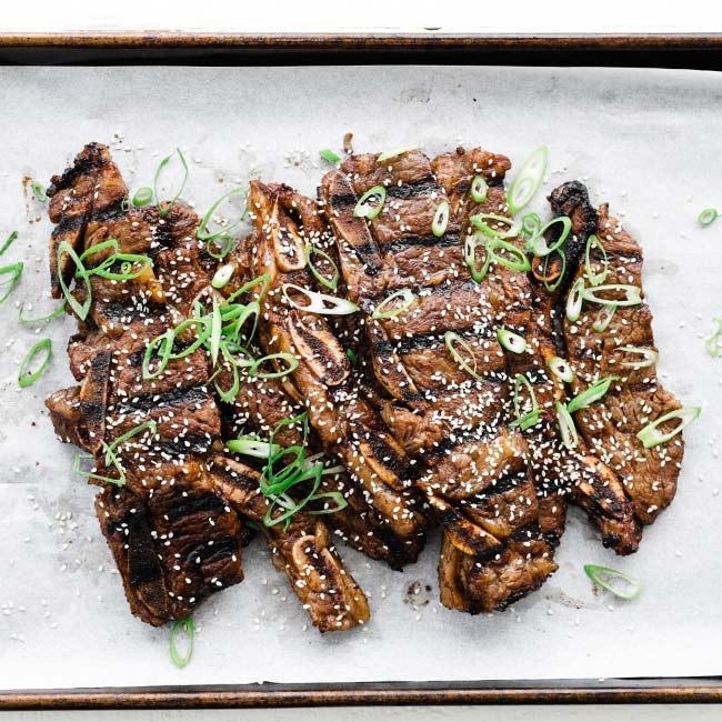 grilled short ribs on a sheet tray with parchment paper