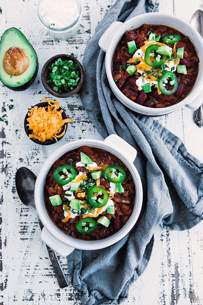 bowls of chili topped off with sour cream and avocados next to other toppings
