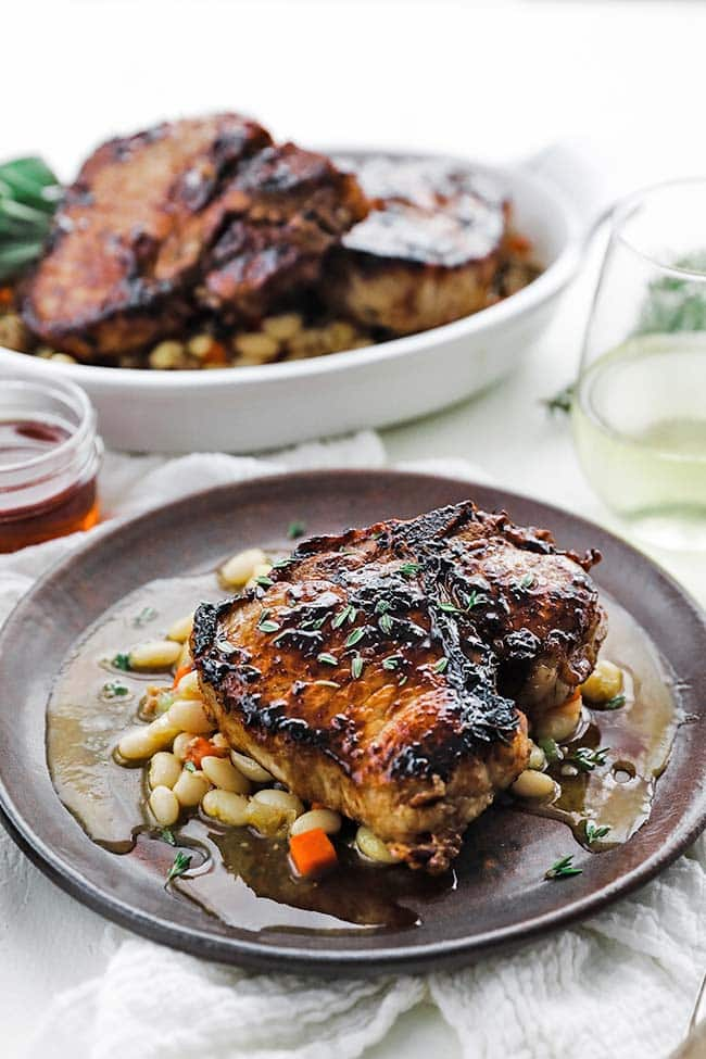 plate of roasted pork chops with white beans and vegetables