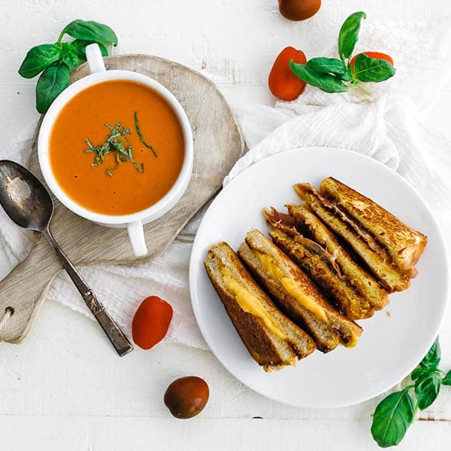 sliced grilled cheese on a plate next to a bowl of tomato soup
