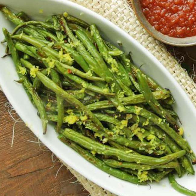 oval dish full of cooked green beans with lemon zest