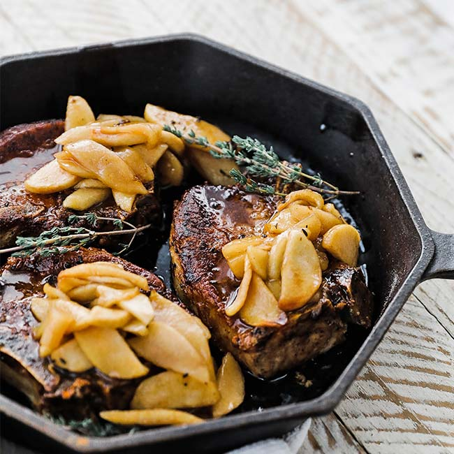 skillet of cooked pork chops with roasted apples