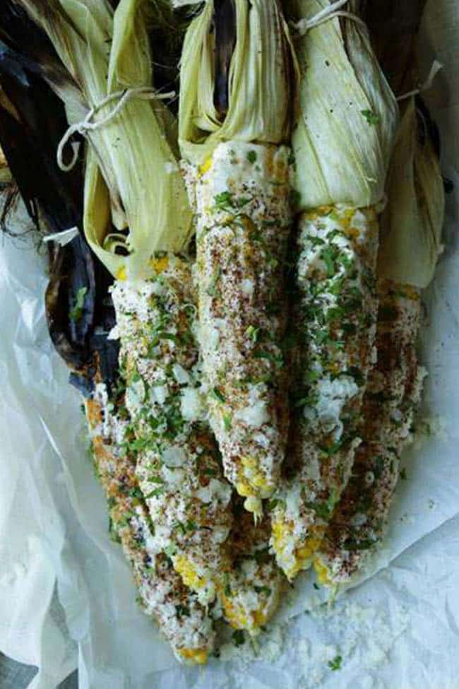 almost shucked corn elote with cheese and chili powder on parchment