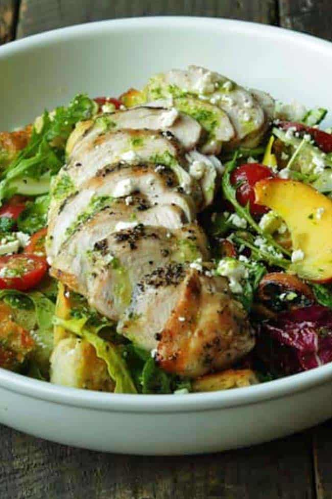 bowl of panzanella salad with grilled chicken and pesto vinaigrette