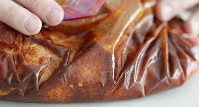 moving the seasoning around with pork tenderloin in a plastic zip bag