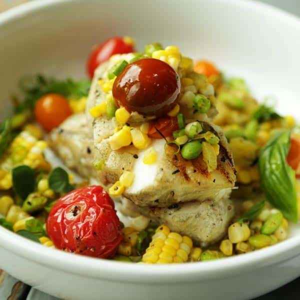 grille sea bass in a bowl with tomatoes, corn and hatch chiles