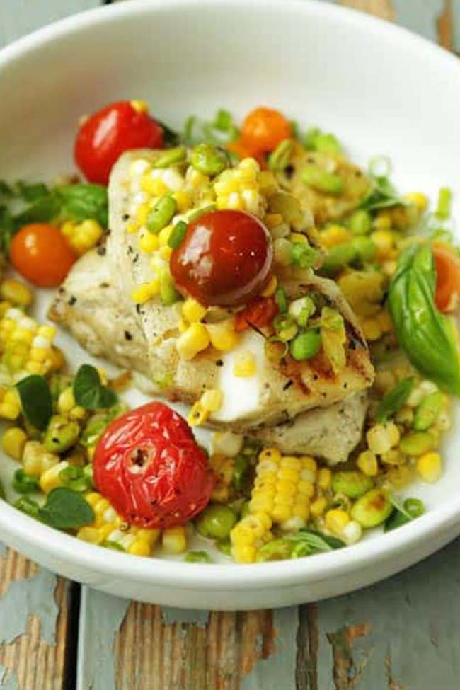 fish with cooked cherry tomatoes, roasted corn and herbs in a bowl