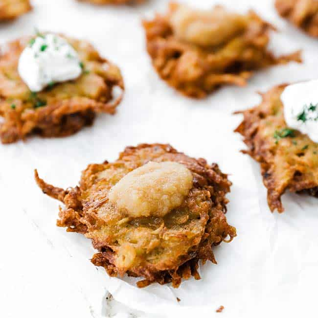 potato latke on a parchment paper with apple sauce on top