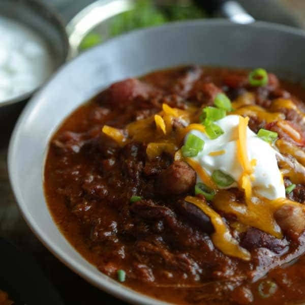 a close up video of a loaded Texas Style Chili Recipe with Slow Cooked Brisket and shredded cheddar cheese, green onions and sour cream