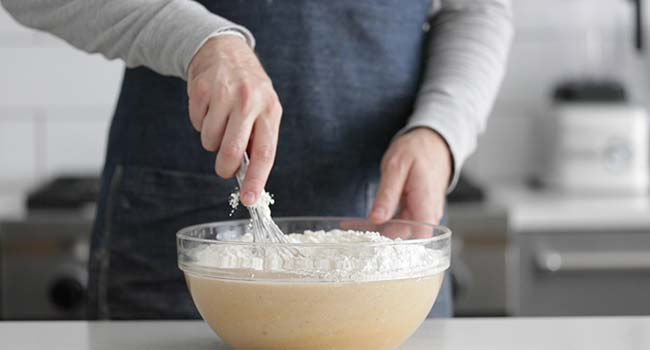 whisking flour in a bowl with melted butter and eggs