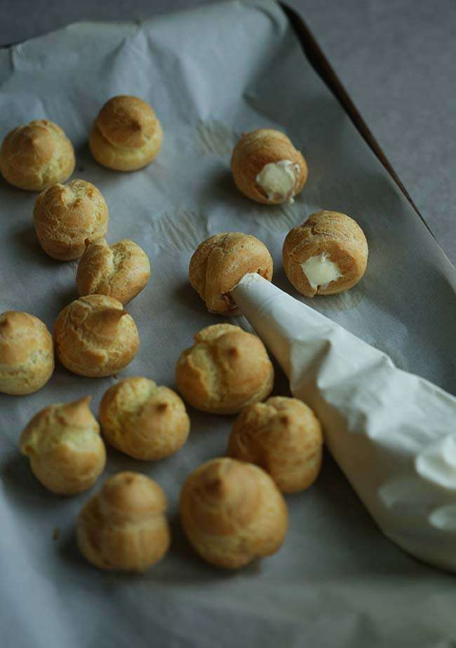 stuffed baked cream puffs with bavarian cream in a piping bag