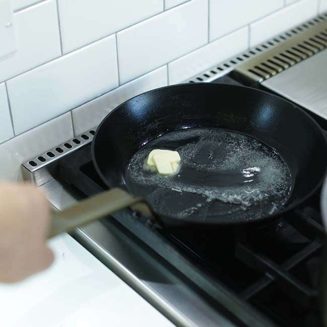 swirling around melted butter in a saute pan for cooked green beans