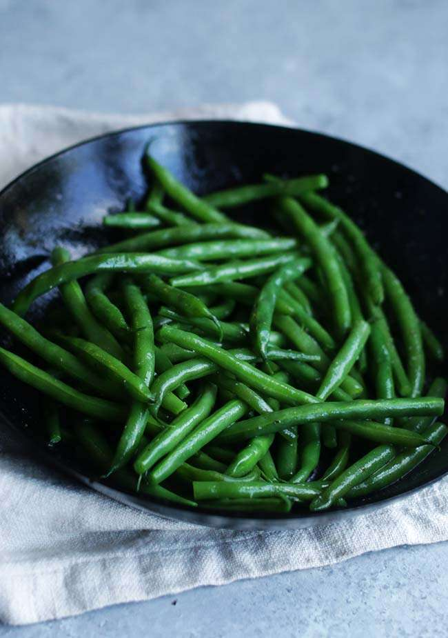 cooked butter glazed green beans in a frying pan