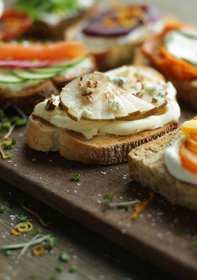 A close up photo of a gourmet toast recipe with pears, creme fraiche and blue cheese