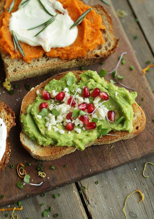 close up photograph of avocado toast with queso fresco and pomegranate seeds