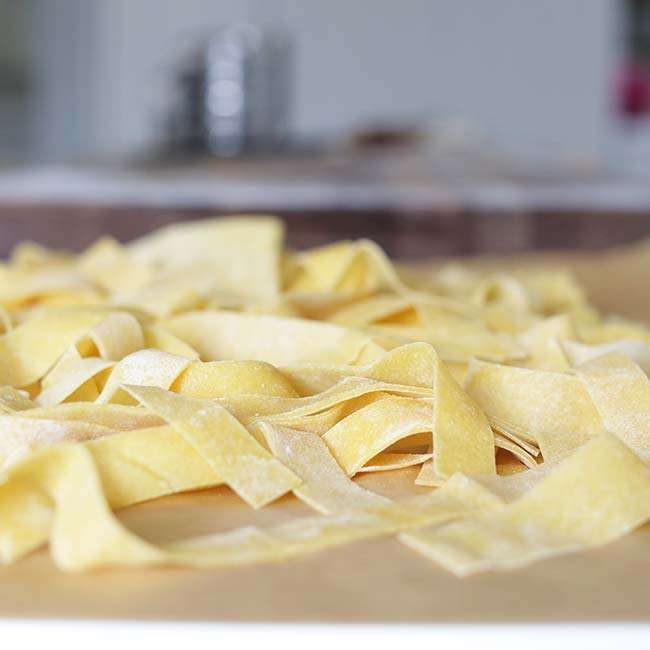 homemade pappardelle pasta with flour on parchment paper