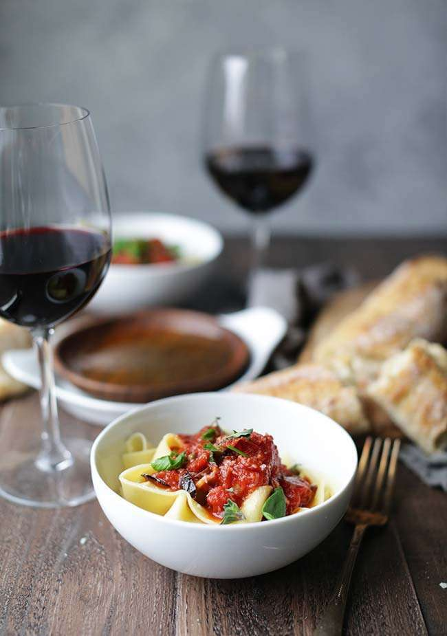 bowl of pasta with tomato sauce with bread and red wine