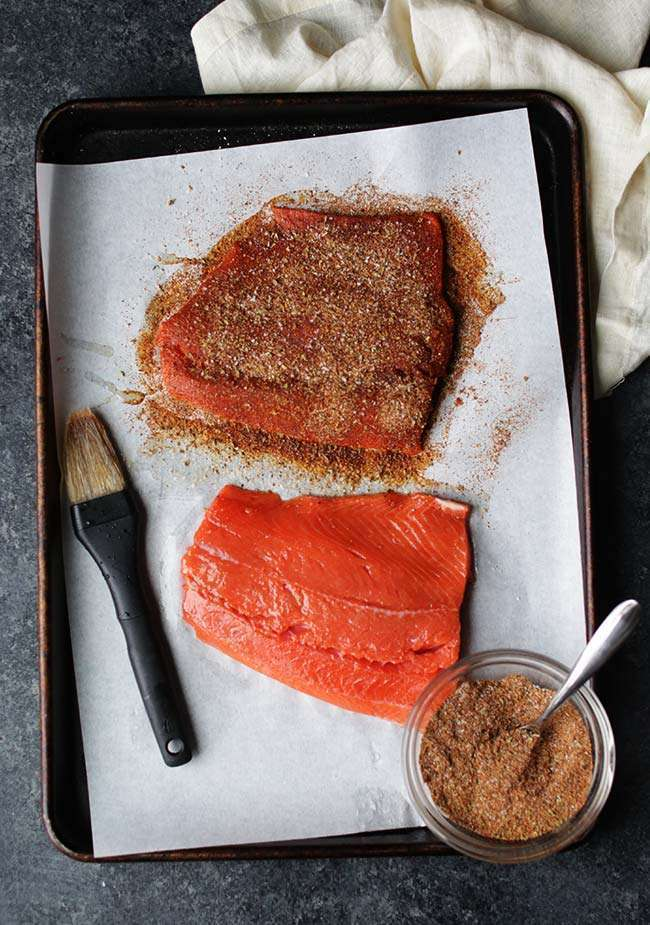 salmon fillets on a sheet tray with a brush of olive oil and spicy rub