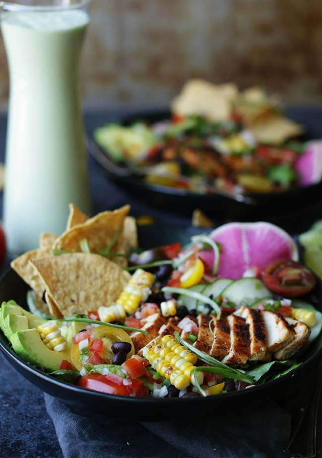 bowl of taco salad with tortillas, corn and chicken with a jar of avocado lime dressing