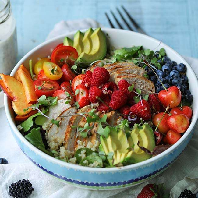 blue bowl of full of lettuce, berries, chicken avocado and tomatoes