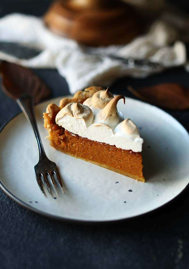 slice of sweet potato pie with marshmallow merengue on a small plate with a fork