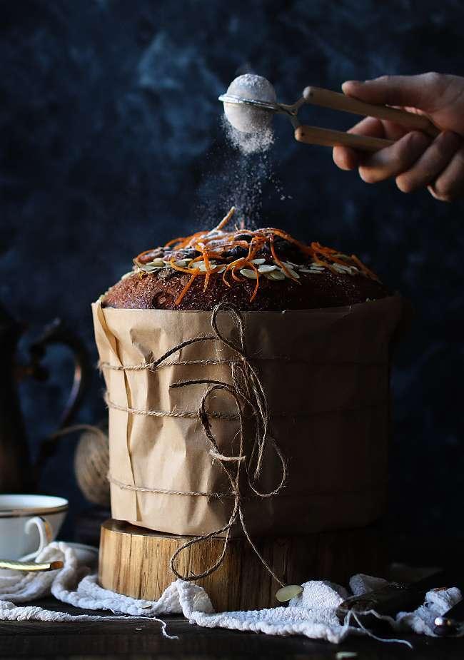 sprinkling powdered sugar onto a panettone bread cake recipe