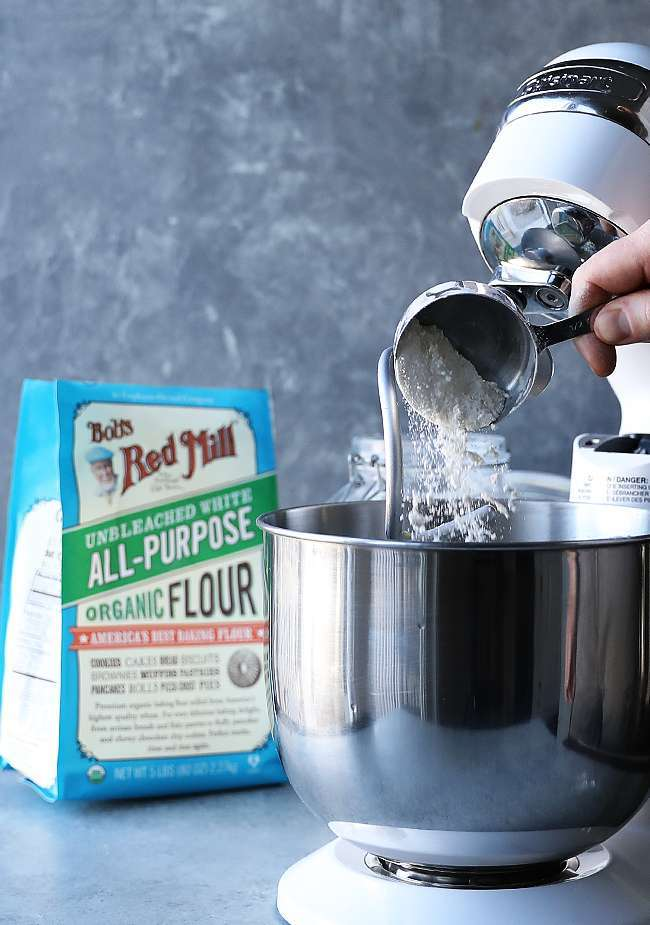 adding flour to a stand mixer with the hook attachment
