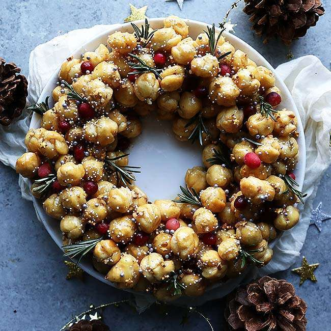 Homemade Struffoli Recipe with Honey and Pecans on a plate and decorated with rosemary, sprinkles and cranberry