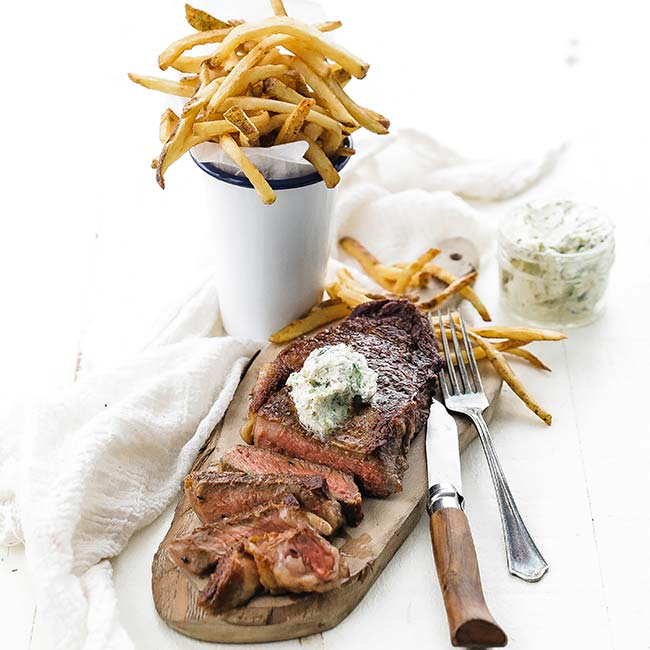 slice steak with butter and fries on a cutting board