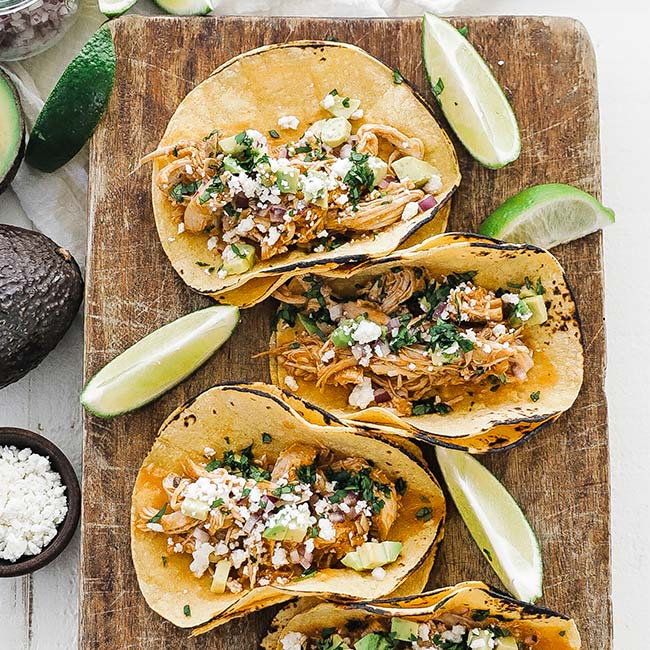 cutting board with 3 chicken tinga tacos and limes