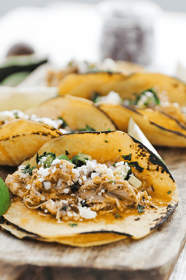 chicken tinga tacos with cheese and lime on a cutting board