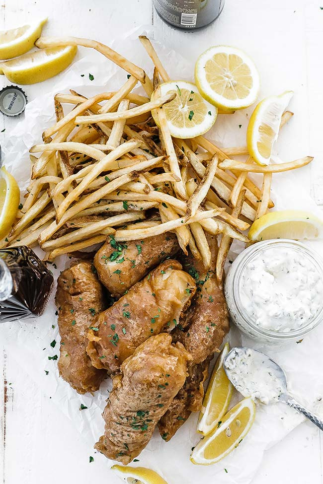 french fries, fried fish, lemons and tartar sauce