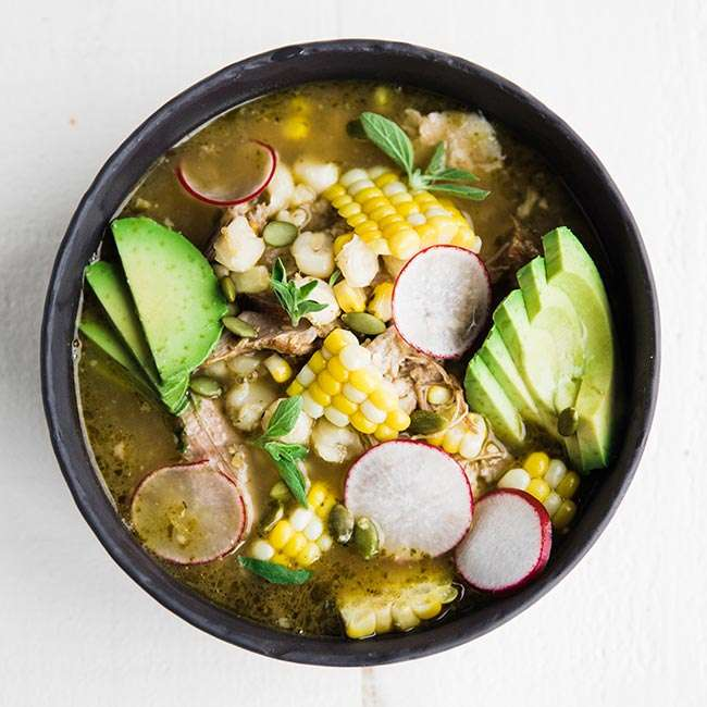 verde pork posole recipe in a bowl served with corn and avocado