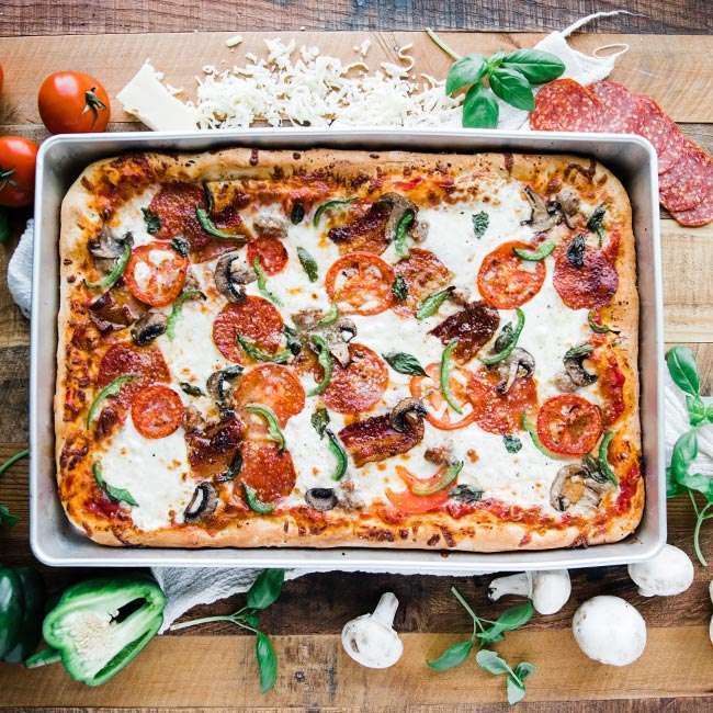 sicilian pizza in a sheet pan with cheese, tomatoes, peppers and mushrooms