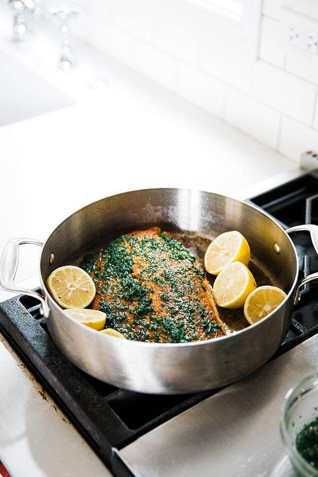 salmon in a pan with herbs and lemon