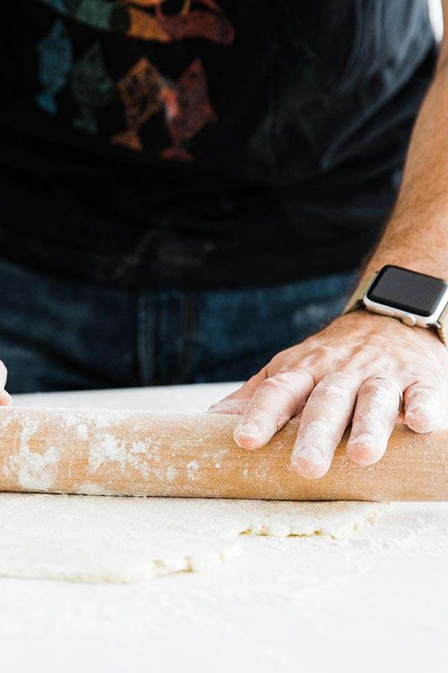 rolling out homemade pie crust on a counter top with a rolling pin