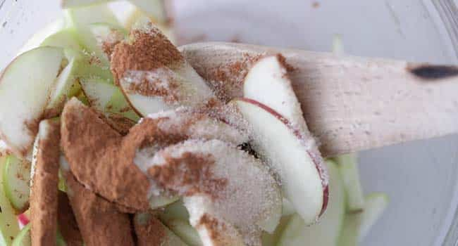 mixing sliced apples with cinnamon and sugar in a bowl
