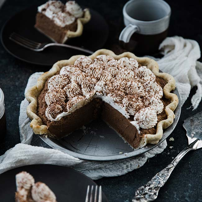 french silk pie recipe in a pie tin with whipped cream and chocolate shavings