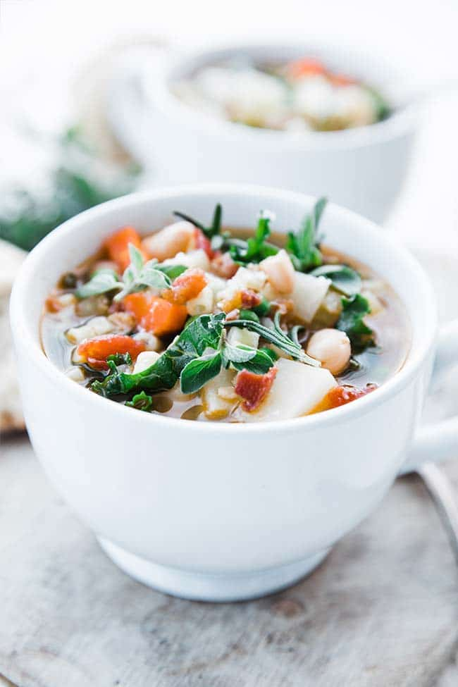 vegetable minestrone soup recipe with beans, kale, carrots and oregano in a cup
