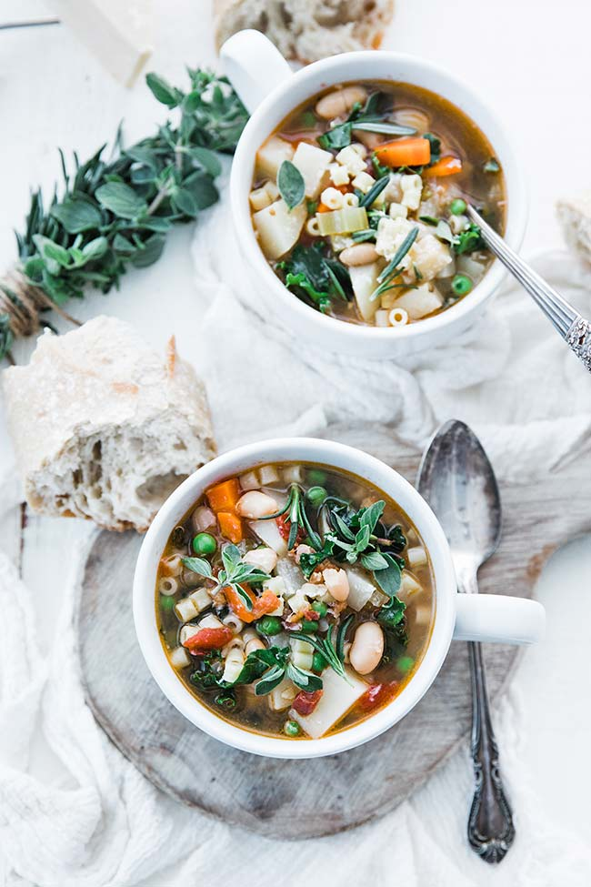 vegetable minestrone soup served in a large cup with herbs and bread