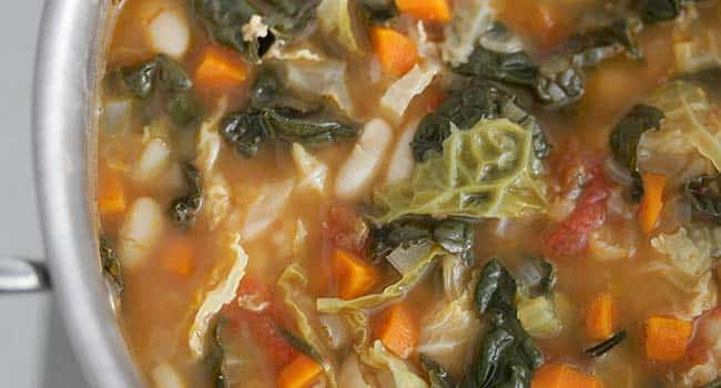 simmering kale and cabbage with vegetables in broth in a pot